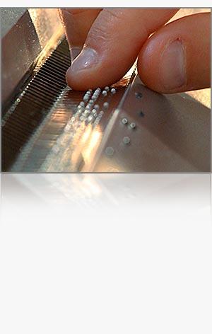 Detailfoto Zeigefinger mit einer Braillezeile auf der Tastatur